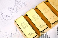 Photo of gold bars on graphs and statistics, studio shots